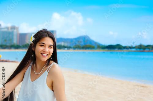 Teen girl sitting on Hawaiian beach, Diamond Head in background