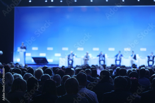 Foto Rear view of Audience over the speakers on the stage in the conference hall or s