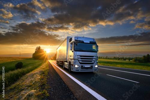 Fototapeta premium Ciężarowa jazda na asfaltowej drodze w wiejskim krajobrazie przy zmierzchem z ciemnymi chmurami