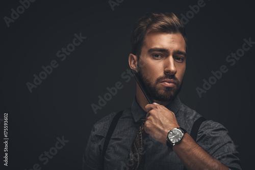 Obraz na plátně Handsome man combing beard