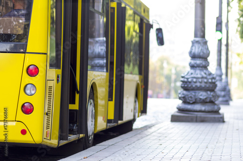 Modern yellow city bus with open doors at bus station