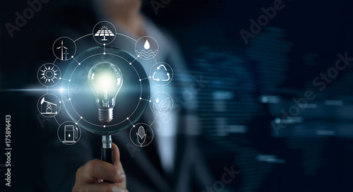 Canvas-taulu Man holding magnifying glass and light bulb ,searching global show the world's c