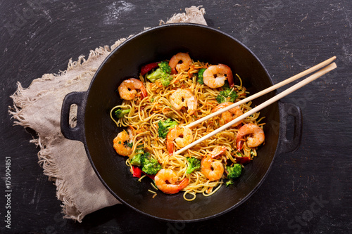 Stir fried noodles with shrimps and vegetables in a wok
