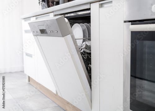 Open dishwasher with clean dishes in white kitchen