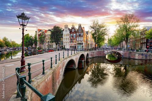 Fototapeta premium Domy nad kanałem amsterdamskim na zachodzie słońca, Holandia