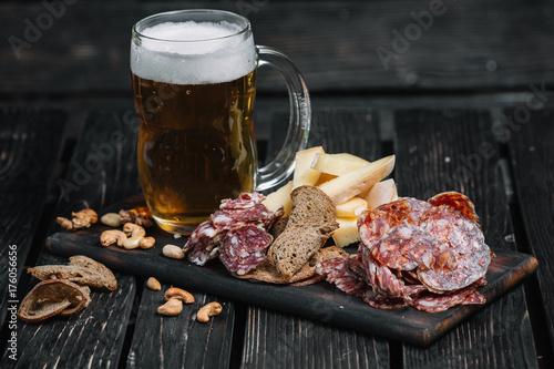 Mug of beer and snacks on wooden board on dark wood background. Kielbasa, cheese, nuts, toasts