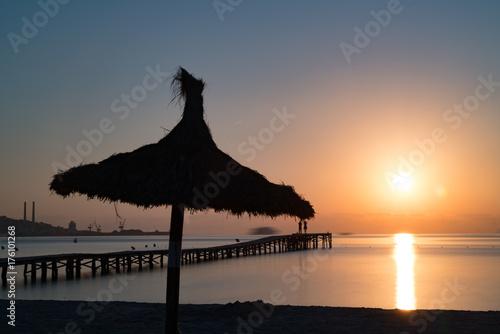 Beach parasols  on sunset sky