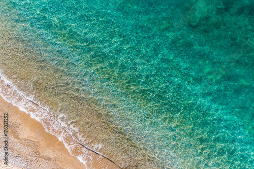 Waves of turquoise color roll on the sandy beach aerial view