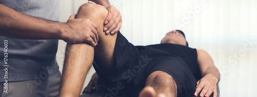 Asian male therapist giving massage to lower back pain patient in clinic
