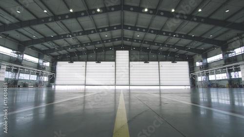 Fotografia Roller shutter door and concrete floor inside factory building for industrial background