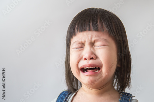 Canvas Print Portrait of little asian crying girl with little rolling tears weeping emotion,