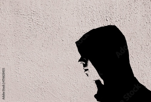 Young teenage bully boy in black hoodie with graffiti stencil effect on white concrete textured wall