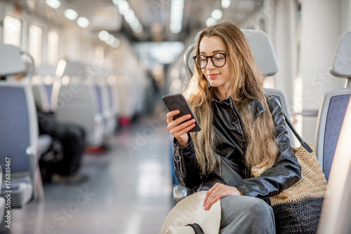 Lifestyle portrait of a young businesswoman sitting with smart phone at the modern train