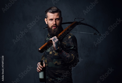 A man holds the craft beer bottle and a crossbow. Fototapeta