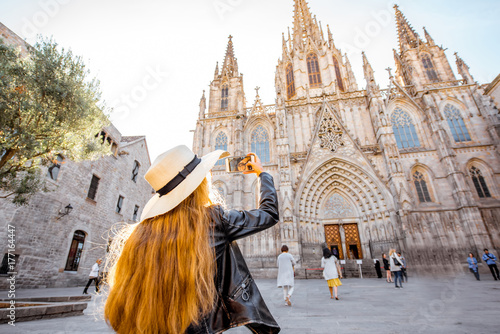 Fototapeta premium Młoda kobieta turysta fotografowanie z telefonem słynnego kościoła świętej Eulalii podczas rana w Barcelonie