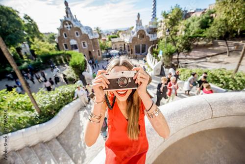 Fototapeta premium Turystka w czerwonej sukience podczas wizyty w słynnym parku Guell w Barcelonie
