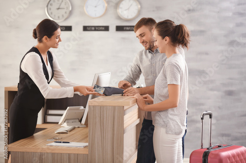 Photo Young couple paying for hotel room at reception