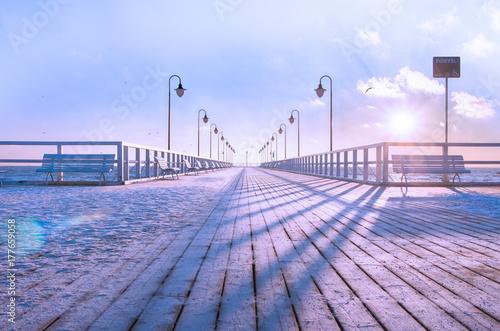 Fototapeta premium Drewniane molo, pokryte świeżą warstwą śniegu, zimowy poranek.
