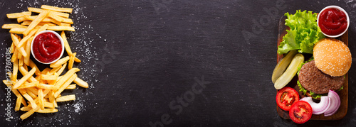 hamburger with french fries on dark background