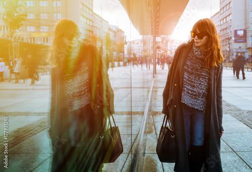 Obraz na płótnie Woman walking on street and looking at shopping window
