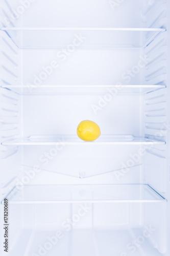 Lemon in empty clean refrigerator, inside