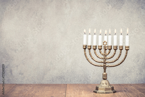 Obraz na płótnie Bronze Hanukkah menorah with burning candles on wooden table front old vintage concrete wall background