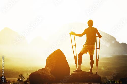 Obraz na płótnie Disabled man stands crutches mountains backdrop