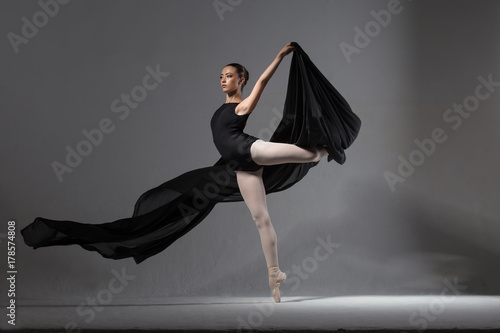 Photo Graceful ballerina in black tights posing with black cloth