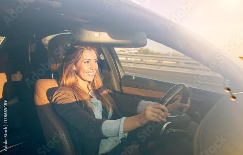 Fotografia Beautiful businesswoman driving car at sunset