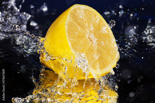 Lemon Slices falling deeply under water with a big splash on blue background