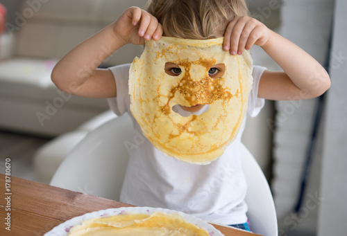 Little boy with a pancake instead of a mask on the face
