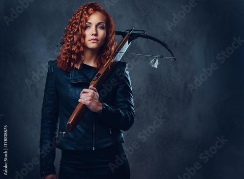 Foto Redhead female  holds crossbow.