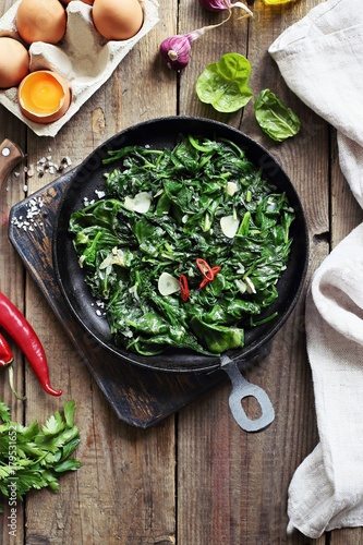 Stewed spinach. Making of baked eggs with spinach and tomatoes. Overhead view.