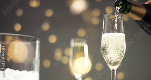 Photo Bottle of sparkling wine with three flute glasses with bubbles floating up on gr