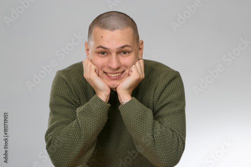 Obraz na plátne A young man is skinhead in a green military style sweater
