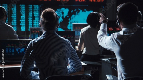 Fotografering Financial traders working in modern office analyzing statistics and driving trade on exchange