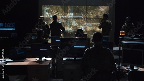 Fotografiet Group of soldiers or spies in dark room with large monitors and advanced satellite communication technology launching a missle