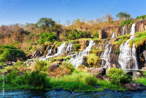 Fototapeta Kaskadowy wodospad wśród skał i roślinności ścienna
