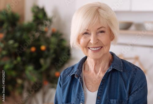 Fototapeta Cheerful elderly woman standing in the kitchen