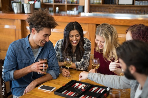 Fotografia Friends playing backgammon while having drinks in bar