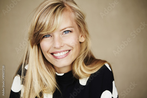 Foto Blue eyed and blond woman smiling to camera, studio
