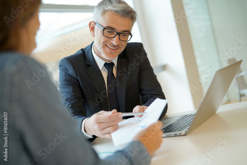 Woman in banker's office signing financial loan for project Fototapeta