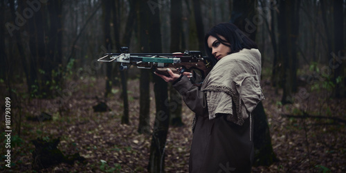 Foto Girl with a crossbow in the forest. Autumn forest.