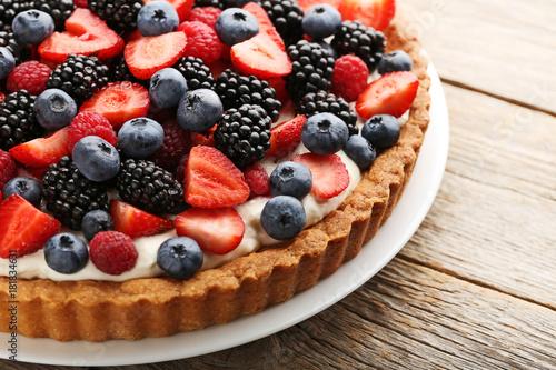 Sweet tart with berries in plate on grey wooden table Fototapeta