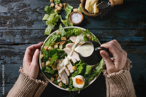 Obraz na płótnie Female hands powring dressing to Classic Caesar salad with chicken breast in white ceramic plate