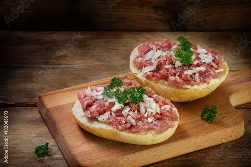 german mettwurst brotzeit, minced pork sausage with onions and parsley garnish on buns, cutting board on a dark rustic wooden background, copy space