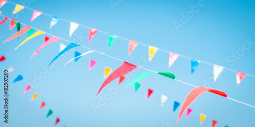 Tablou Canvas Fair flag blur bunting background hanging on blue sky for fun festa event, summe
