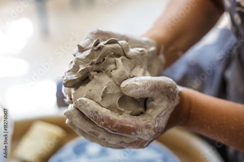 Fotografia Female potter hands knead wet white clay
