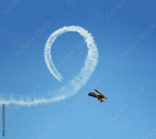 Fotografering Vintage biplane does loop stunt with smoke trails