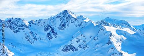 Fototapeta premium Góry w śniegu. Panorama zima krajobraz z szczytami i niebieskim niebem